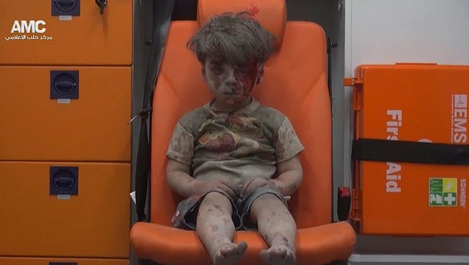 In this frame grab taken from video provided by the Syrian anti-government activist group Aleppo Media Center (AMC), a child sits in an ambulance after being pulled out or a building hit by an airstirke, in Aleppo, Syria, Wednesday, Aug. 17, 2016.