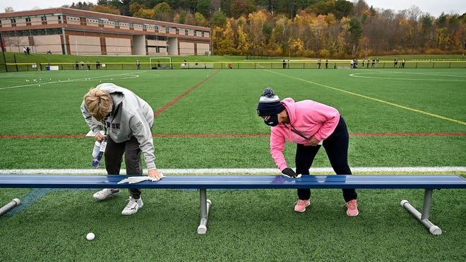 Lincoln-Sudbury assistant athletic director Judy Katalina (left) and Deb Riggott wipe down a bench in between field hockey games Saturday.
