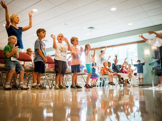 Students and volunteers dance to music in the opening group meeting at the third week of the Everest vacation Bible school program at Christ Lutheran Church in Dallastown on Wednesday. Following a pledge, singing and dancing, students broke up into small groups for activities.