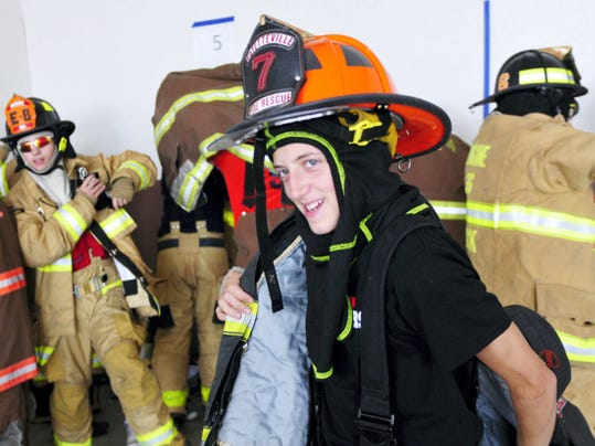 Peyton Buselli, 14, puts on his turnout gear with others at the Franklin County Public Safety Training Center Monday during the week-long Junior Firefighter Academy.
