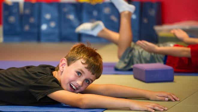 Nathaniel Perry, 8, of Evansville, laughs in between poses during Curious Adventure with Miss Amy, a children's yoga class offered at the Tri-State Athletic Club in Evansville, Sunday, Sept. 18, 2016. The club plans to offer children's yoga once a month.