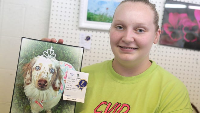 Marion County Fair volunteer, Sierra Fields, holds up one of her award winning photographs in the activities barn.