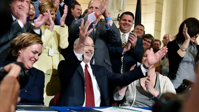 Pennsylvania Gov. Tom Wolf cheers after signing the Medical Marijuana Act into law Sunday, April 17, 2016, in the Pennsylvania State Capitol Rotunda in Harrisburg. Medical marijuana advocates gathered to celebrate as Pennsylvania became the 24th state in the country to legalize marijuana for medical use. The law takes effect in 30 days.