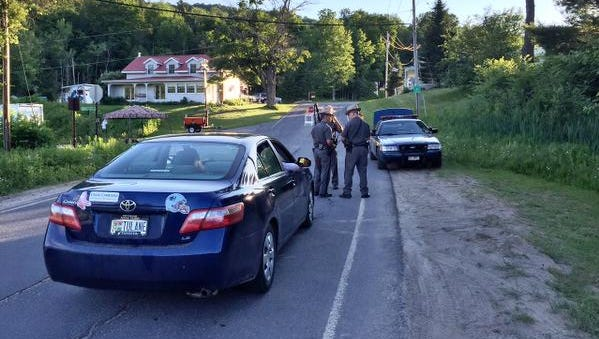 Police officers hold a roadblock on New York State Route 41 in Franklin County, N.Y., on Friday evening, June 26, 2015, during the manhunt for escaped prisoners and convicted murderers Richard Matt and David Sweat. During a news conference several hours later, the authorities said police shot and killed Matt on Friday, but Sweat remained on the run.