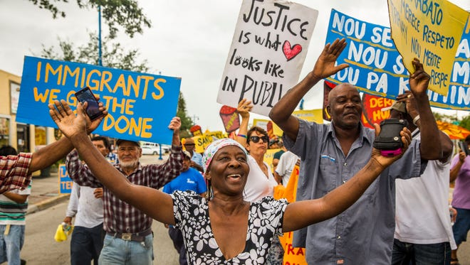 Yolan Louseren chants and marches with other residents through the streets of Immokalee for International Workers' Day on Monday, May 1, 2017.