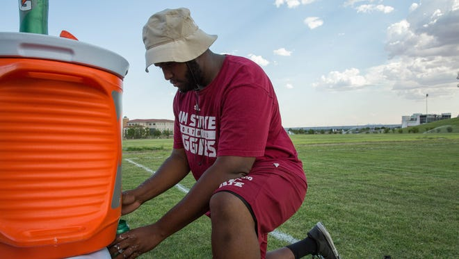 Keanu Higgins a volunteer defense line assistant coach, fills up water bottles as he and others from the New Mexico State Aggies football team mark the field at the Pat and Lou Sisbarro Community Park at NMSU, Wednesday, June 21, 2017. Temperatures rose into the triple digits Wednesday and will continue that trend the rest of the week.
