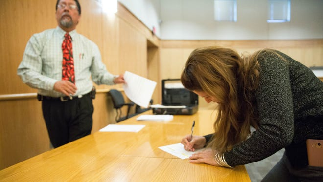 Gema Morales registers for the Doña Ana County Property Tax Auction, Friday Dec. 15, 2017 at the Doña Ana County Government Center. During the auction, properties in the Santa Teresa Country Club again failed to find a bidder.