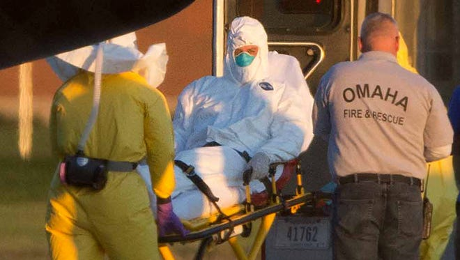 Ashoka Mukpo is loaded into an ambulance after arriving in Omaha, Neb. Mukpo, a freelance video journalist who contracted Ebola while working in Liberia, was taken to Nebraska Medical Center, where he will be treated for the deadly disease.