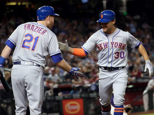 New York Mets' Michael Conforto (30) is greeted by Todd Frazier after Conforto hit a solo home run against the Arizona Diamondbacks during the sixth inning of a baseball game Thursday, June 14, 2018, in Phoenix.