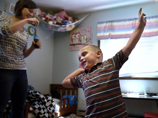 Trent Korpela reacts with happiness July 31, when it's time to play with bubbles while working with Sarah Brixius of Behavioral Dimensions at his home near South Haven.