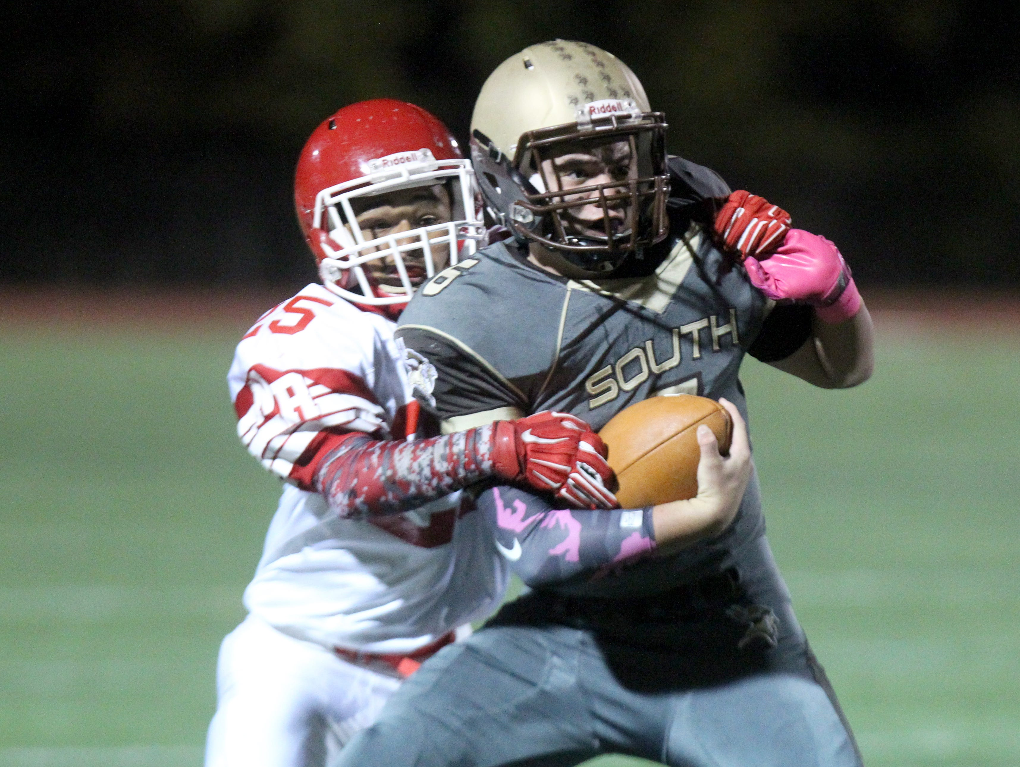 Clarkstown South's Matt Jung is tackled by North Rockland's Michael Cintron during their Class AA qualifying round game at Clarkstown South Oct. 16, 2015.