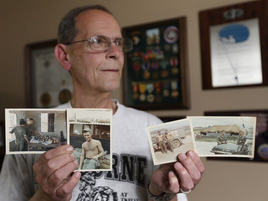 Vietnam veteran John Vandehaar of Des Moines holds up some of the old photographs of him and the base camp where he served during the Vietnam War.