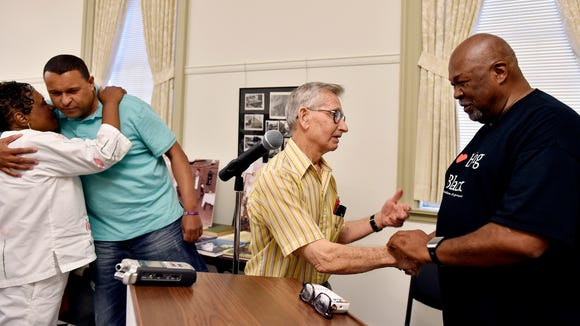 John Seville, of York Township, center, greets Jeff Kirkland after Kirkland's presentation on York's black history. At left, Kirkland's cousin, Lyndon Kirkland of Danbury, Connecticut, greets their aunt, Brenda Rice of York, on Saturday at the York County History Center. Jeff Kirkland, a former York City school board president, is forming the York African-American Historical Preservation Society and presented a lecture on York's black history.
