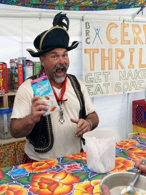 """Luc """"Cap'n Crunch"""" Fournier, 55, of San Francisco, grins at the camera while serving free breakfast to people who stopped by the Cereal Thrillers camp at Burning Man on Thursday, Aug. 31, 2017."""