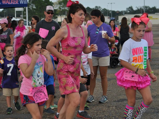 Mary-Kate Leddy, 8, (left) and Anna-Clare Leddy, 10, (right) lead the way as Komen supporters run Saturday in the 5th annual Pink Dress Run in Alexandria. The Leddy sisters ran for their grandma, a breast cancer survivor of 30 years.