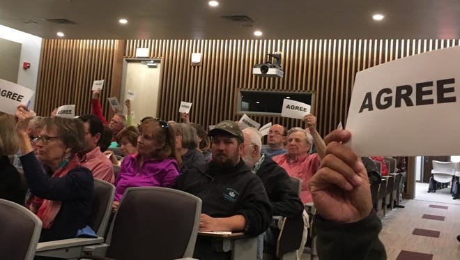 Attendees at a town hall meeting in Green Bay Tuesday  indicate their support for a comment a speaker made about Rep. Mike Gallagher. Gallagher did not attend.