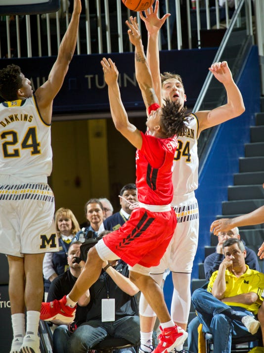 Rutgers guard Corey Sanders, center, has his shot attempt blocked by Michigan guard Aubrey Dawkins (24) and forward Mark Donnal (34), in the second half of an NCAA college basketball game at Crisler Center in Ann Arbor, Mich., Wednesday, Jan. 27, 2016. Michigan won 68-57. (AP Photo/Tony Ding)