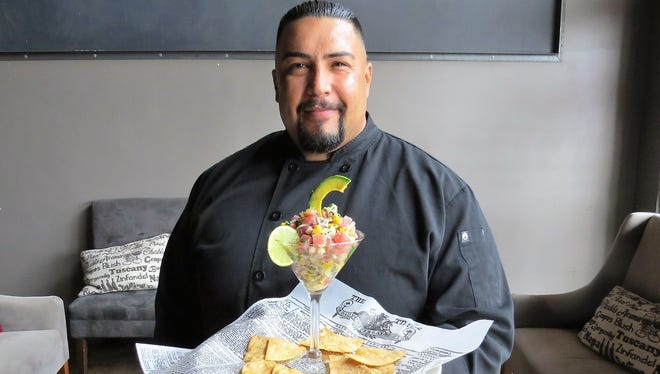 "Chef Julio Perez poses with a happy-hour plating of ahi tuna ceviche at Julian's Restaurant & Bar, the Camarillo restaurant opened by family members after the closing of their Verona Trattoria just a few doors away. ""At Verona's, everything had to be Italian, European. Here, I can do what I really like to do, which is cook everything,"" Perez says."