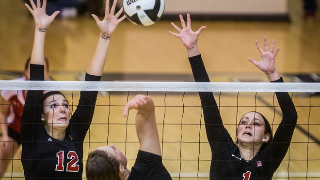 Wapahani's Skyler Vannote (1) and Chase Curry (12) jump to block a hit from Madison-Grant during their regional game at Madison-Grant High School Tuesday, Oct. 27, 2015.