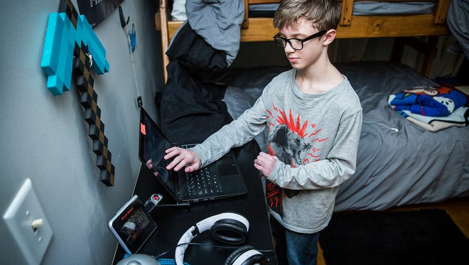 Devin Kidd works on a music track on his laptop in his family's home in Muncie.