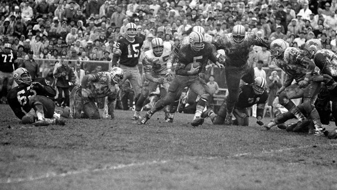 Halfback Paul Hornung of the Green Bay Packers (5) is faced with opposition from Detroit Lions players as he carries the ball down the field to set up his successful field goal in the fourth quarter of their game in Green Bay,  Oct. 7, 1962.  Behind Hornung is Wayne Walker (55).  In center is Roger Brown (76) and right is Darris McCord (78).