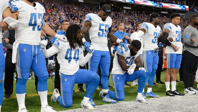 The Detroit Lions' Jalen Reeves-Maybin (44) and Steve Longa (54) kneel during the national anthem before the game against the Minnesota Vikings on Sunday.