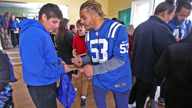 Edwin Jackson, right, signed an autograph for Christian Perez at the Peace Learning Center in Nov. 2017. Members of the Indianapolis Colts and IMPD visited the center to work with 50 sixth graders from IPS #34,  doing team-building sessions designed to teach safe and simple ways to manage anger, solve problems and develop an understanding of differing perspectives.