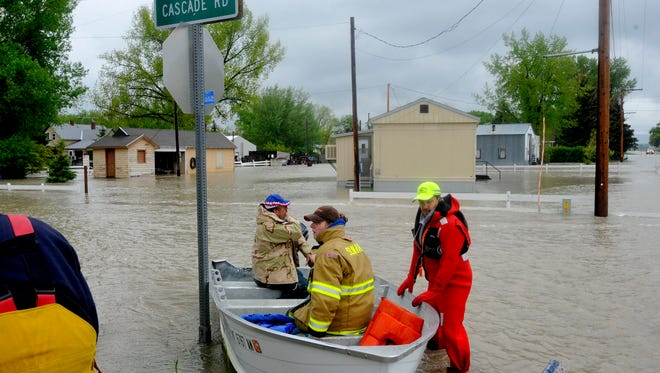 Sun River Volunteer Fire Fighters float the town of Sun River in 2011 to check the wellbeing of residents who decided to stay in their homes through the flooding.