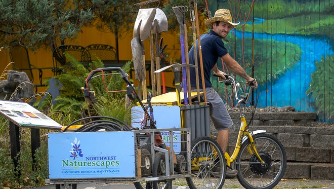 Alden Gray runs his landscaping business with the use of a three-wheeled bicycle poses at a client call at the First Alternative Co-op in Corvallis.