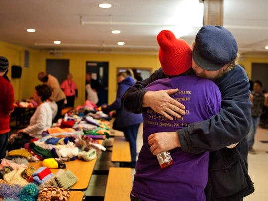 Volunteer Stacey Isenberg hugs David Wright during a winter clothing giveaway Saturday at East Shore Leadership Academy in Port Huron.