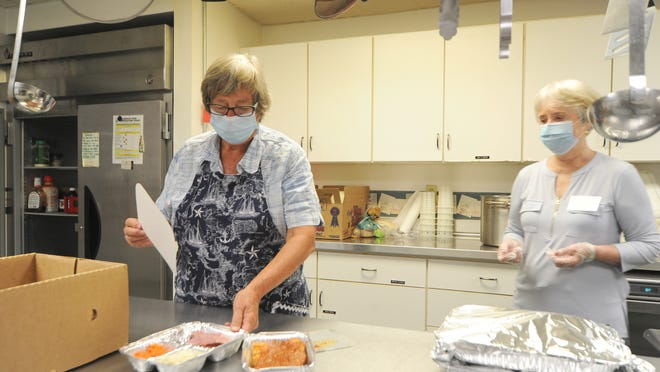 Volunteer Eleanor Winch, left, of Eastham, shows the two meals, corned beef and lasagna, available for takeout Tuesday from the St. Joan of Arc Parish Center kitchen in Orleans. Barbara Strakele, director of Lower Cape Lunch, was instrumental in restarting the interfaith program, which had shut down for months because of the pandemic.