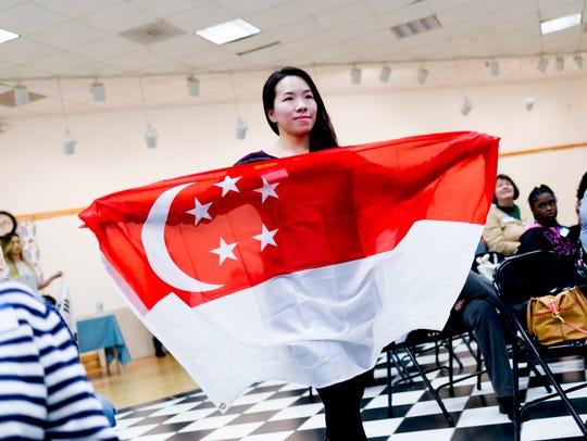 Shirley Elkins carries her Singapore flag during the