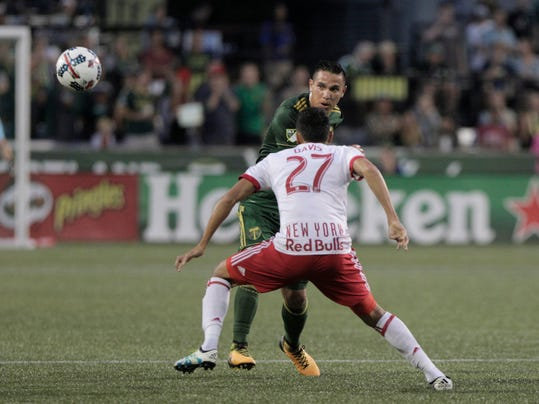 Portland Timbers' David Guzman (20) passes the ball ahead as New York Red Bulls' Sean Davis defends during an MLS soccer match in Portland, Ore., Friday, Aug. 18, 2017. (Sean Meagher/The Oregonian via AP)