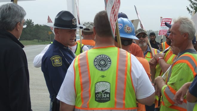 A Michigan State Police trooper talks to picketers outside the Arbor Hills landfill on Tuesday. State and Northville Township officers were present, along with security guards hired by the landfill owner, Advanced Disposal.