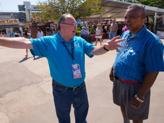 Wisconsin State Fair Park board chair John Yingling (left) gives directions to fairgoer Sam Julks at Wisconsin State Fair Park in West Allis.