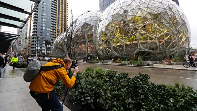 Alex Crook, a photographer with Seattle Magazine, photographs the Amazon Spheres in downtown Seattle on the day of their grand opening, Monday, Jan. 29, 2018, in Seattle. (AP Photo/Ted S. Warren)