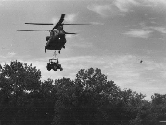 A National Guard helicopter airlifts a tractor to the