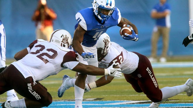 MTSU's I'Tavius Mathers (4) powers through the arms of Alabama A&M's Bryan Brower (32) and Kenneth Davis (52).