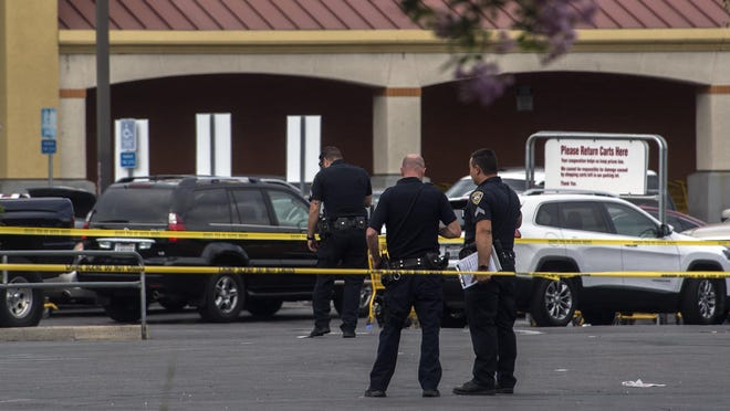 Stockton police officers look for evidence in the parking lot of the Food 4 Less on Hammer Lane near Lower Sacramento Road in Stockton after a shooting nearby.
