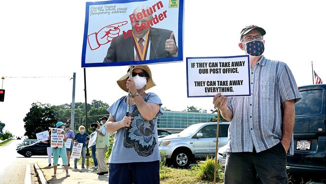 Andrea Bird, left, of Framingham, holds up a photograph of Postmaster General Louis DeJoy as she and Ralph Hebb, also of Framingham, rally in support of the U.S. Postal Service Tuesday afternoon in front of the main Framingham Post Office on Cochituate Road (Rte. 30). DeJoy has denied claims that he was working to undermine mail delivery.