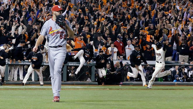 St. Louis Cardinals' Michael Wacha (52) walks off the field as San Francisco Giants' Travis Ishikawa reacts after hitting a walk-off three-run home run during the ninth inning of Game 5 of the National League baseball championship series on Thursday night.