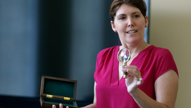 Former detective from Buffalo and guest speaker Lissa Redmond, shows a magnifying glass given to her as she makes her presentation to the Murder on Ice group of Western New York, which writes about murder mysteries, during a meeting at the Legacy at Parklands.
