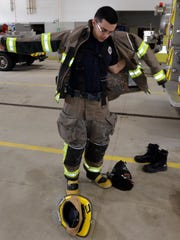 Lyon Township firefighter Doug Moebs tries on some of the New Hudson station's new gear, purchased with help from a FEMA grant. Lyon Township's previous firefighter suits were more than 10 years old and deficient in many safety areas.