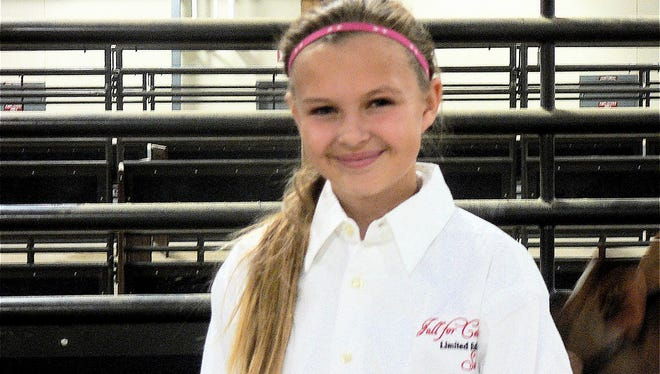 """Natalie Roe, 13, Monticello, bid on and bought her first calf, a Brown Swiss bred by Voegeli Farm. """"I was really scared,"""" she said."""