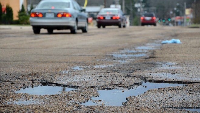 This file photo shows traffic on a pothole-ridden street in Jackson.