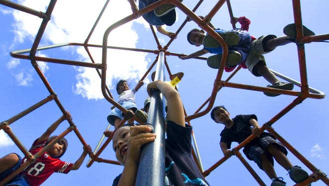 "In this file photo, children play on a monkey bars during the ""Fun in the Sun"" summer camp program."