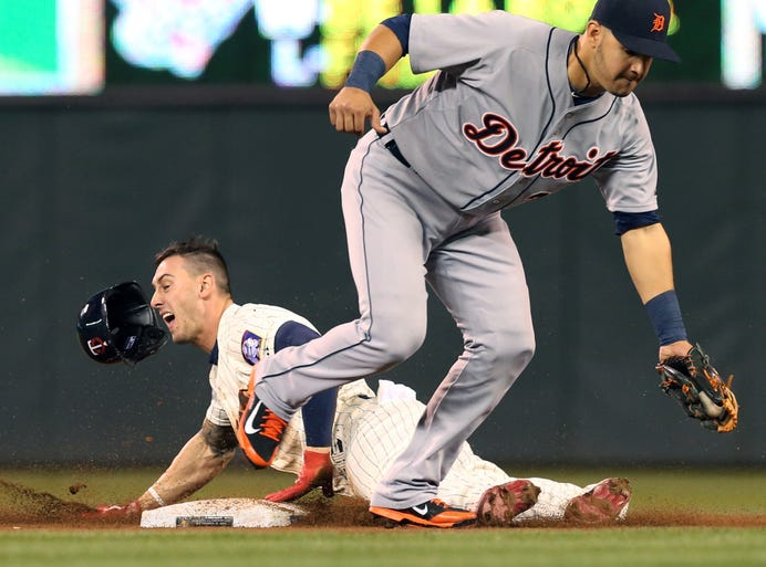 Minnesota Twins' Jordan Schafer, left, loses his helmet as he steals third on Detroit Tigers shortstop Eugenio Suarez in the eighth inning of their game in Minneapolis Wednesday Sept. 17, 2014. The Twins won 8-4.