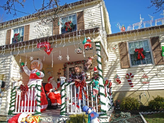 Harry Christensen sits on the front porch of his Glasgow-area home where he has been decorating for Christmas for years.