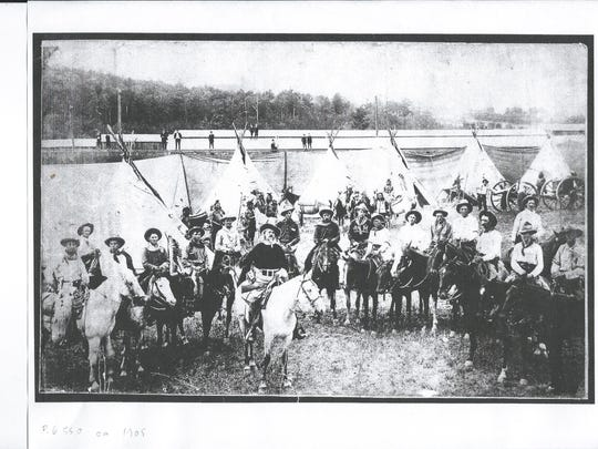 Buffalo Bill sits on a white horse and Freckles is at far left, alson on a white horse, in this vintage photo of the Buffalo Bill Wild West Show.