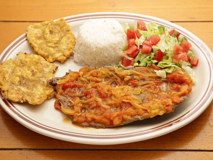 The carne en bistec con platano from La Tiendita includes tender, sauce-coated steak, rice, and patacones.